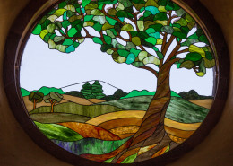 Stained glass showing a madrone tree and Southern Oregon landscape